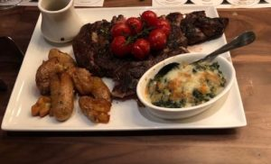 A 25 oz, bone-in rib eye with blistered tomatoes, crispy potatoes, spinach gratin/butternut squash at Cooper's Hawk Esquire Chicago. (J Jacobs photo)